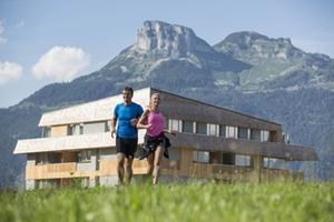 Laufendes Paar mit Hotel und Loser im Hintergrund